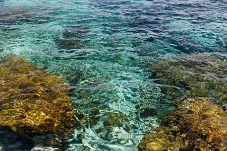 Clear waters of mediterranean sea with turquoise and emerald colors being vibrant next to the stones with gold tone