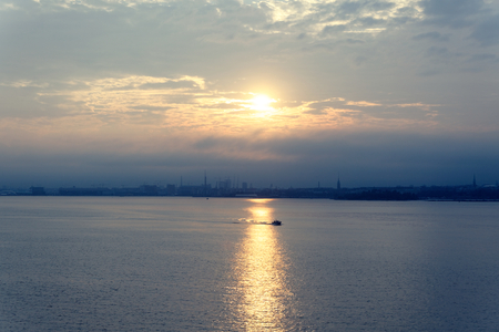 Distant landscape of Helsinki from Gulf of Finland with calm sea and ship crossing the sea with the sun glare from the cloudy sunset
