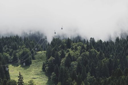Cable cars lifting into the fog of the summit clouds Reklamní fotografie
