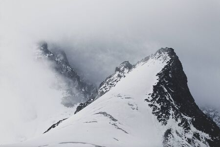 Mountain summits with glaciers covered with clouds and mist in the Swiss Alps