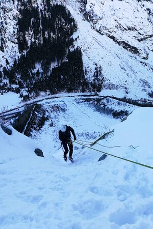 Climber rappelling down into the valley in the winter Austrian Alps