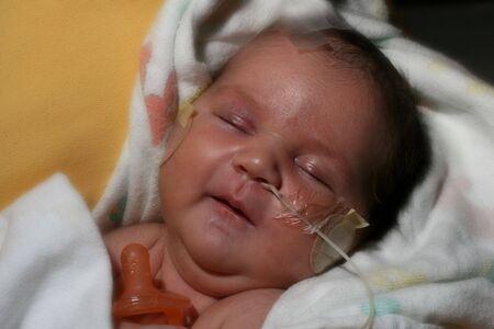 smiling, sleeping newborn baby in the ICU