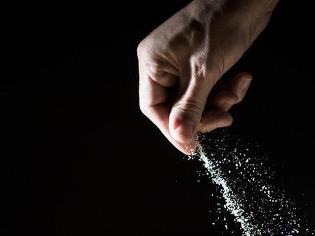Hand verschütten eine Prise Salz vor schwarzem Hintergrund
