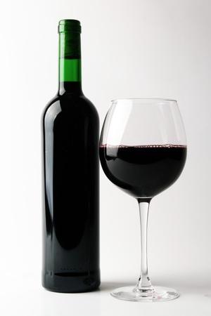botella de licor: Botella de vino y un vidrio en un fondo blanco