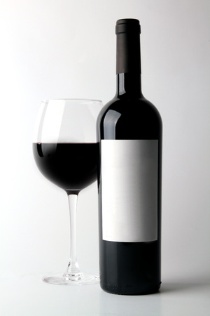 Bottle of red wine with glass and white label Foto de archivo