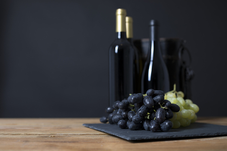 Wine Bottle with grapes in a traditional environment in a black background