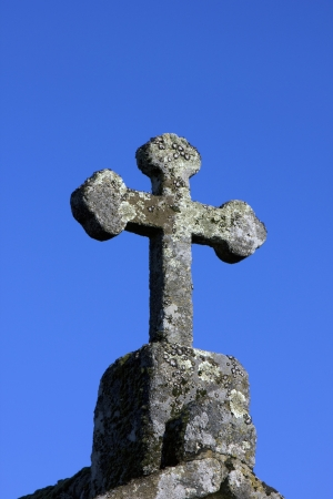 Stone cross on deep blue sky Stock Photo