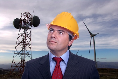 man portrait construction hat on Eolic energy turbines background Stock Photo
