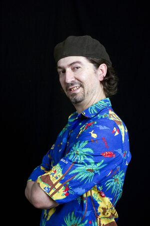 young happy man with a hawaiian shirt on black background  Stock Photo