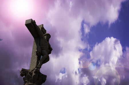 Stone Cross in a cloudy sky Stock Photo
