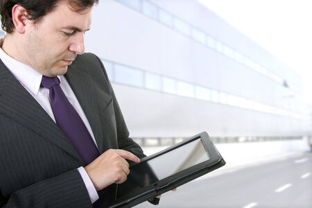 Businessman using a tablet pc with office buildings Stock Photo