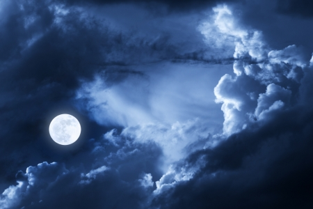This dramatic photo illustration of a nighttime scene with brightly lit clouds and large, full, Blue Moon would make a great background for many uses  illustration