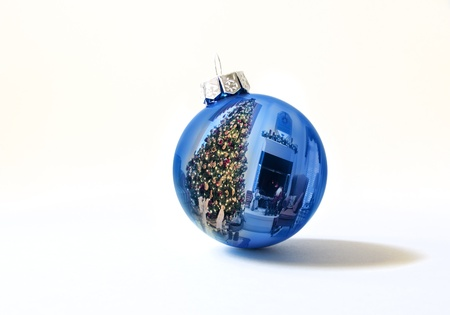 This shiny bright blue Christmas ball ornament reflects a brightly lit Christmas Tree and holiday decorated living room against a white background  I am the sole copyright owner of the reflection photo used in this image