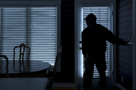 This photo illustrates a burglary or thief breaking into a home at night through a back door  View from inside the residence