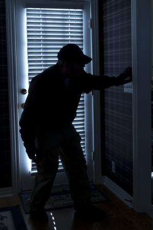 이 사진은 주택 내부에서 다시 문을보기를 통해 밤에 집에 침입 강도 나 도둑을 보여줍니다 스톡 콘텐츠