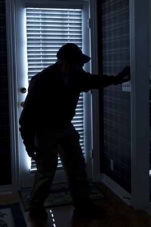 This photo illustrates a burglary or thief breaking into a home at night through a back door  View from inside the residence  photo
