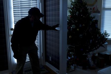 이 사진은 주택 내부에서 크리스마스 휴가 시즌보기 동안 다시 문을 통해 밤에 집에 침입 강도 나 도둑을 보여줍니다