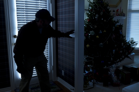 burglary: This photo illustrates a burglary or thief breaking into a home at night through a back door during the Christmas Holiday Season  View from inside the residence