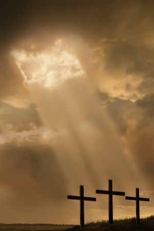 Inspirational religious photo illustration of three large crosses on the top of a hill, a breaking storm, and light beams breaking through the clouds, shining towards the crosses
