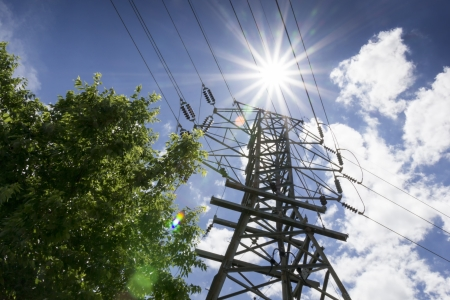 energy use: These high voltage power lines and intensely bright sunlight emphasize the energy requirements of summer with electicity needs for air conditioning and power generation