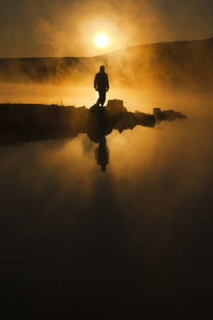 A warm, foggy sunrise silhouettes a hiker against a cold early morning mist across a lake  The mist hung perfectly still in completely calm air almost as a spirit greeting the new day