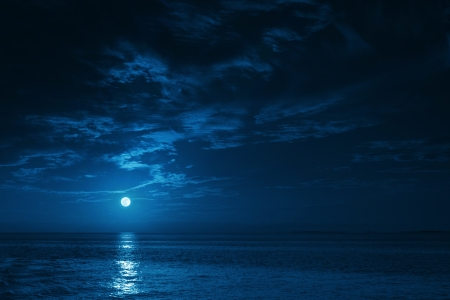 twilight: This photo illustration of a deep blue moonlit ocean at night with calm waves would make a great travel background for any coastal region or vacation, emphasizing the beauty of the night time ocean or sea  Stock Photo