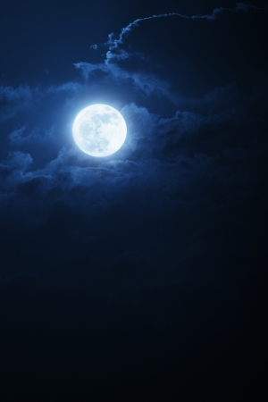 bue: This dramatic photo illustration of a nighttime scene with brightly lit clouds and large, full, Blue Moon would make a great background for many uses