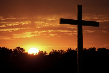 crucify: Inspirational Religious Christian Photo illustration of a Dramatic Sky with Large wooden Cross standing against very saturated colors of bright yellow sun, rich orange clouds, sunlight shafts, and a line of silhouetted trees  Stock Photo