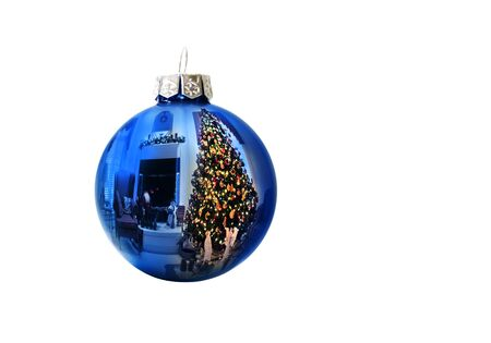 This shiny bright blue Christmas ball ornament reflects a brightly lit Christmas Tree and holiday decorated living room against a white backgoung  I am the sole copyright owner of the reflection photo used in this image  Фото со стока