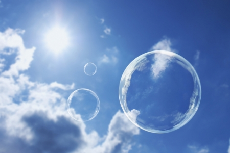 zero gravity: These soap bubbles floats calmly against a clear deep blue sky and clouds representing natural  Stock Photo