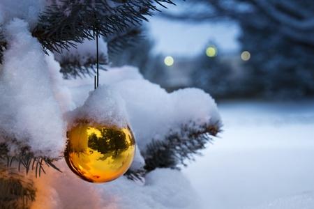 Deze heldere gouden sieraad opknoping van een besneeuwde tak van de Kerstboom weerspiegelt zijn outdoor besneeuwde omgeving Stockfoto