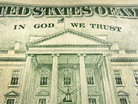 A macro close up photo emphasizing the inscription  In God We Trust  printed on the back of a United States ten dollar bill with selective focus on the words  Фото со стока