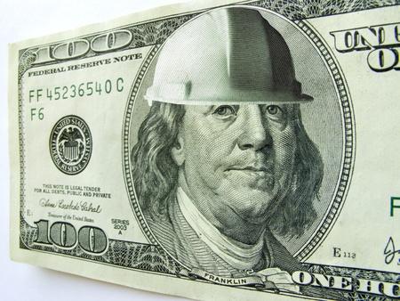 Ben Franklin lleva un sombrero duro en este billete de cien dólares que podrían ilustrar el costo de la construcción o la seguridad en un entorno empresarial o industrial Foto de archivo - 22149466