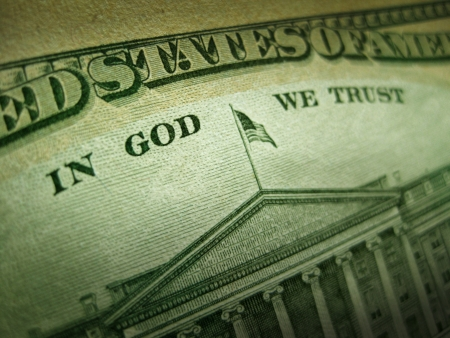 A macro close up photo emphasizing the inscription  In God We Trust  printed on the back of an United States ten dollar bill with selective focus on the work God  photo