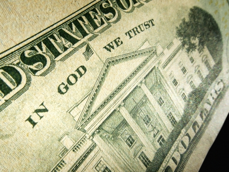 A macro close up photo emphasizing the inscription  In God We Trust  printed on the back of a United States ten dollar bill with selective focus on the words  photo