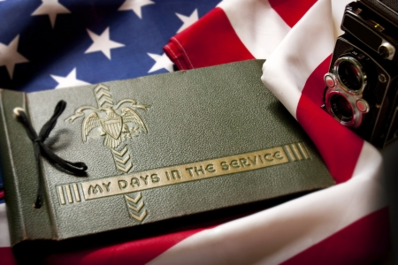 Memorial Day remembrance photo of a World War II  Military Service photo album and antique camera with  United States Flag as a background symbolizes memories of a war veterans