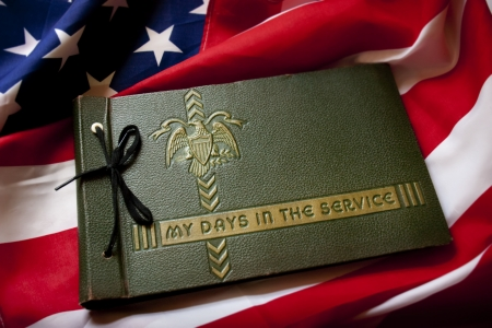 United States Memorial Day remembrance photo of a World War II Military Service photo album with United States Flag as a background symbolizing memories of a war veteran