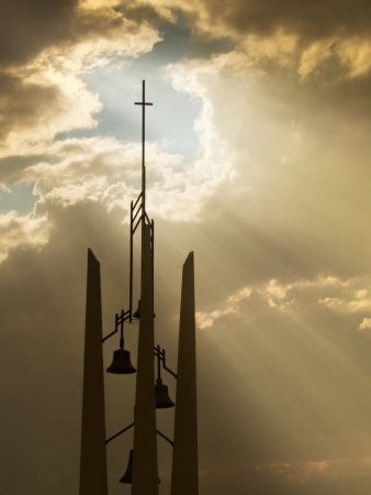 church bells: Sunbeams break through the storm clouds behind this Church Belltower and Cross making an inspirational, christian scene Stock Photo