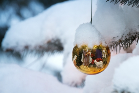 christmas morning: This Christmas Tree Ornament brightly reflects a Nativity Scene with the newborn baby Jesus on a snow Christmas morning outdoors  Stock Photo