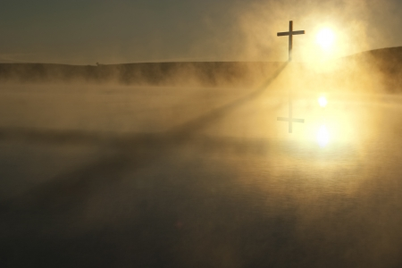 risen christ: This Sunrise Cross on a misty lake casts a lengthy shadow and reflection on this calm Easter Morning Illustration Stock Photo