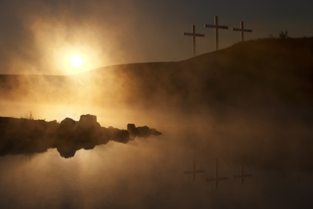 resurrected: Dramatic religious photo illustration of Easter Sunday Morning reflecting a prayerful moment as a warm sun rises over a foggy lake, and three crosses on a hill reflect in the water below