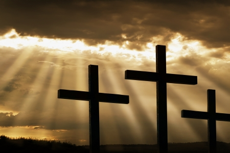 good friday: Dramatic sky silhouettes three wooden crosses with shafts of sunlight breaking through the clouds  A dramatic and inspiring religious photographic illustration for Christian beliefs including Easter and Good Friday