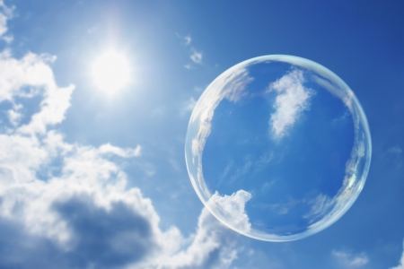 This large soap bubble floats calmly against a clear deep blue sky and clouds representing a natural