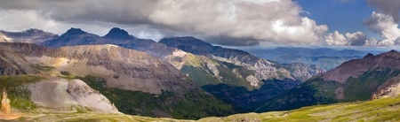 Imogene Pass outside of Ouray Colorado  Billowing clouds, high altitude vegetation, boulders broken by weathering into hand sized rocks, and layering of mountains in the distance make for a beautiful panoramic scene