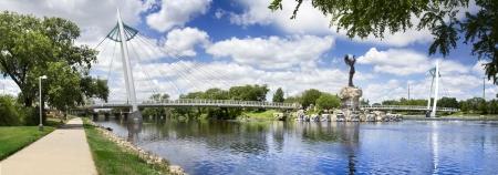 これはカンザス州ウィチタ ダウンタウン近くアーカンソー川を渡って、平野のキーパー像およびフィート橋の写真