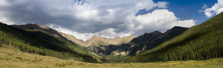colorado rocky mountains: At high altitudes in the Colorado Rockies, the shadows cast by low passing cumulus clouds create hard shadows through the thin atmosphere emphasing the distance of this beautiful scene