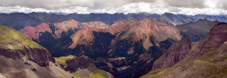 These  red  mountains are the result of a heavy concentration of iron ore  This scene has sheer cliff faces, mountain peaks in the distance and a mining operation Фото со стока - 22177152