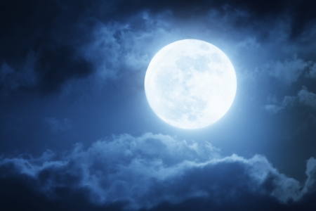 Dramatic Nighttime Sky and Clouds With Large Full Blue Moon  Stock Photo