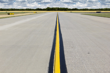 This rural airport taxiway runway photo illustration has a bright yellow center line heading off into the distant horizon which is a golden yellow wheatfield  Nice bright yellow colors and neutral runway