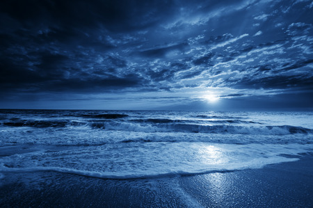 night scenery: a beautiful midnight blue ocean moonrise with dramatic sky and rolling waves